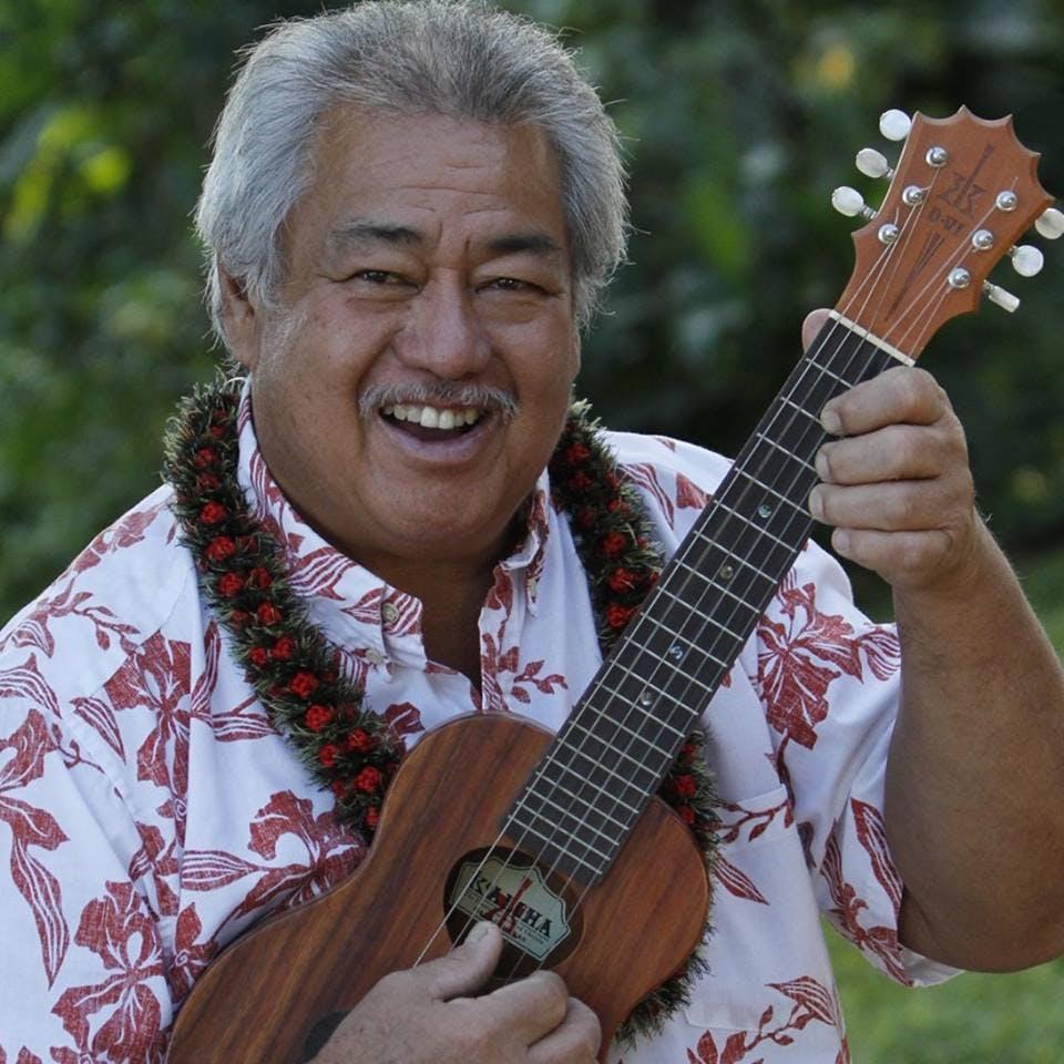 George Kahumoku Jr. holding a guitar