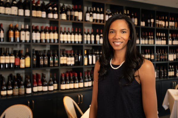 a woman standing next to a bottle of wine