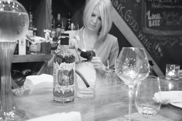 a woman sitting at a table with wine glasses
