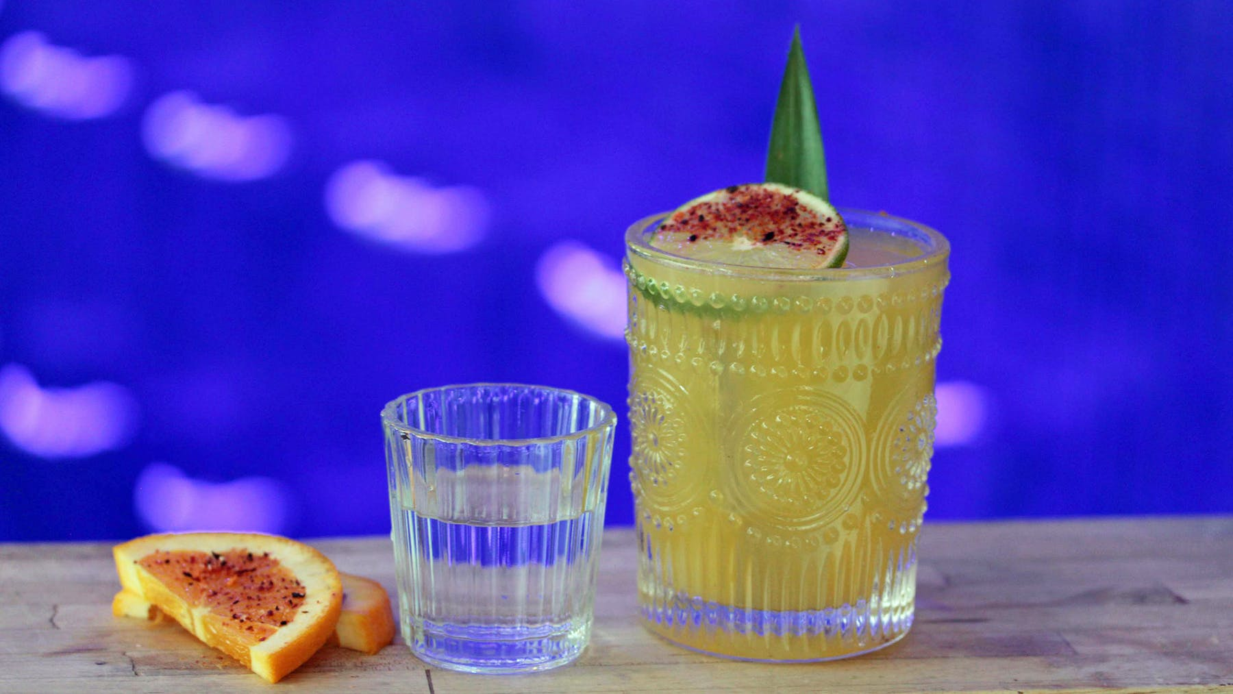 a glass of Margarita, small glass of mezcal and orange slices