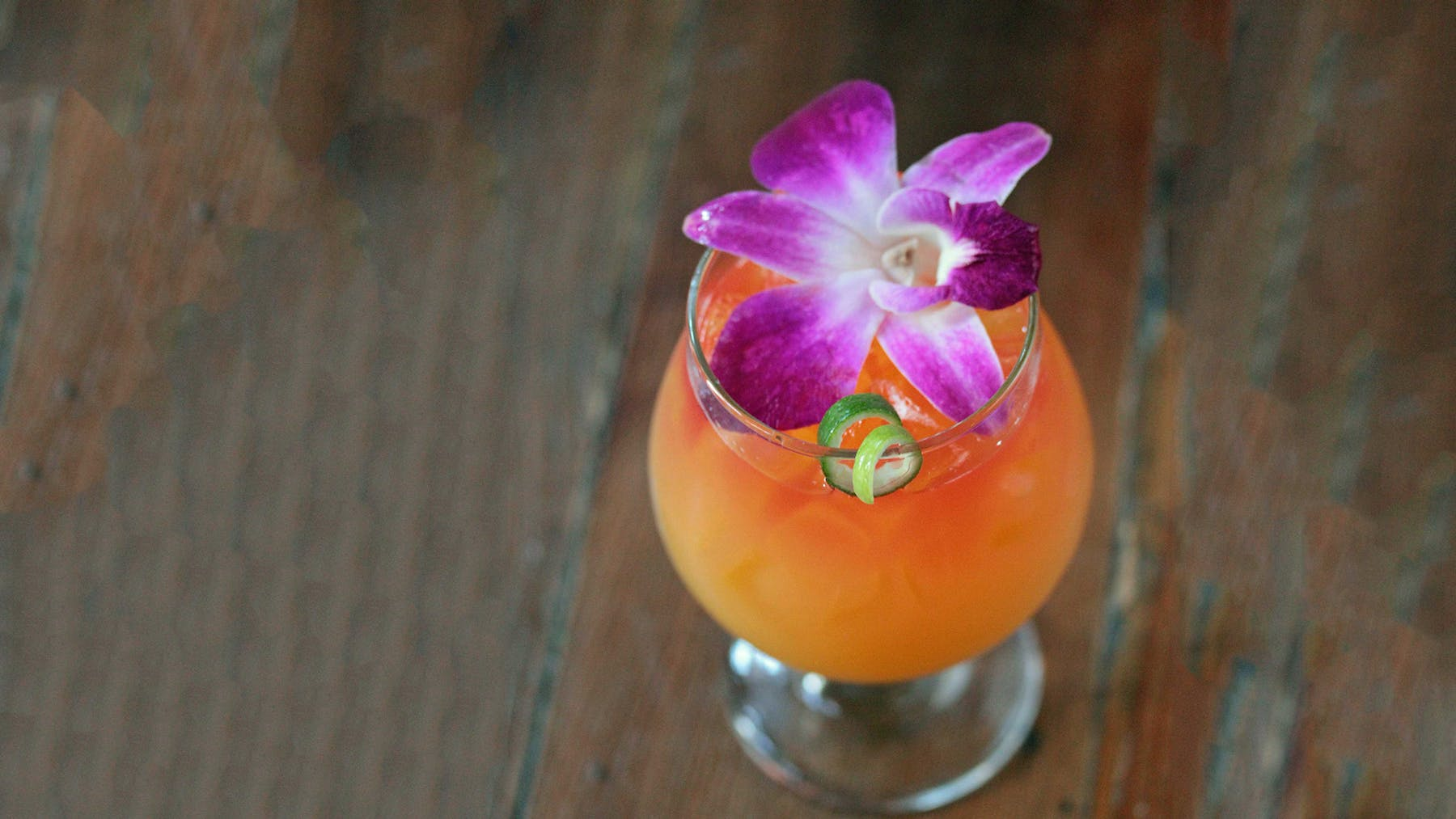 a tropical drink with a flower on top sitting on a table