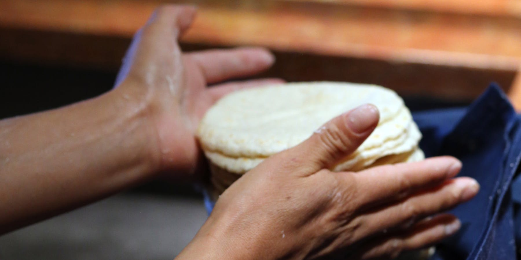 two hands stacking tortillas
