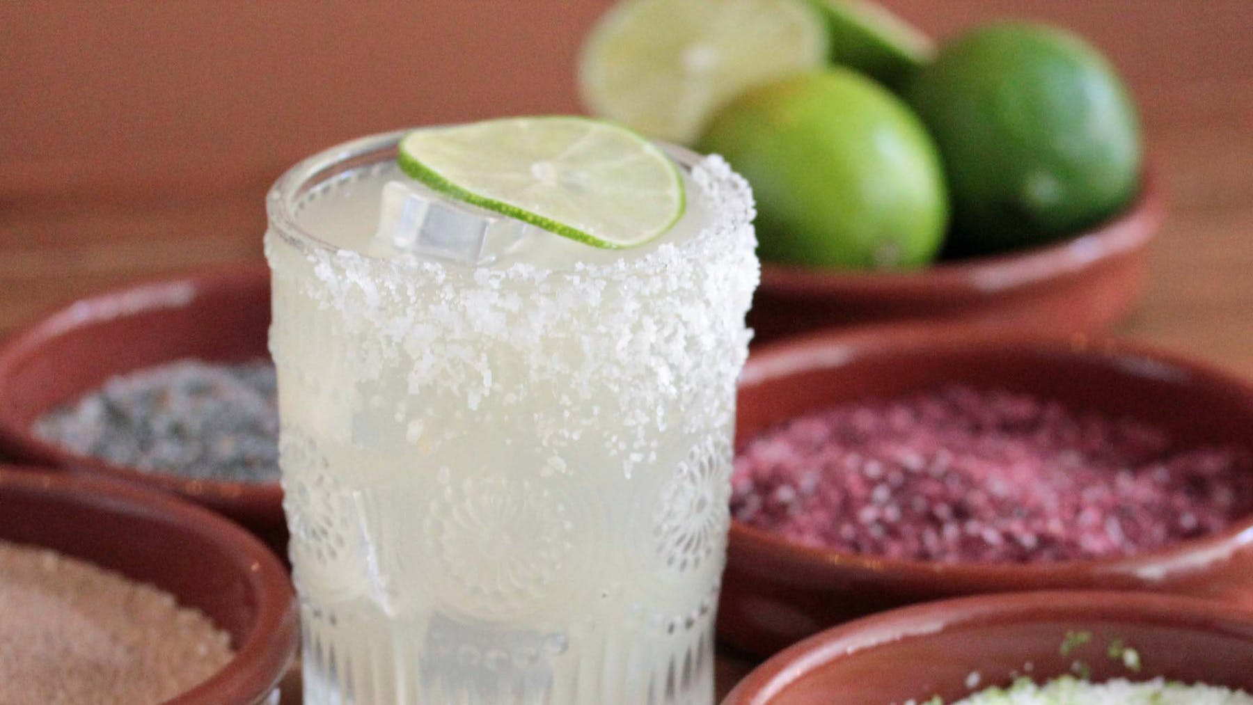 glass of Margarita with salts and bowl of limes