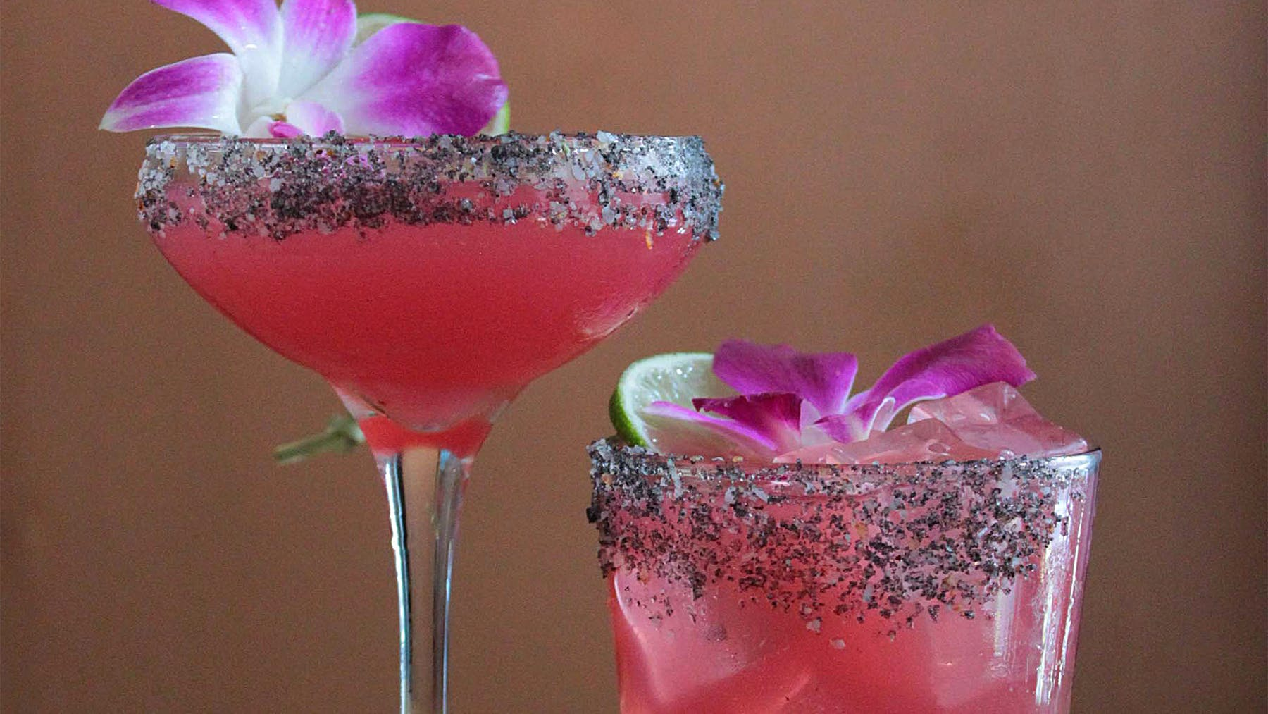 two glasses of Margaritas with a flower and lime on top