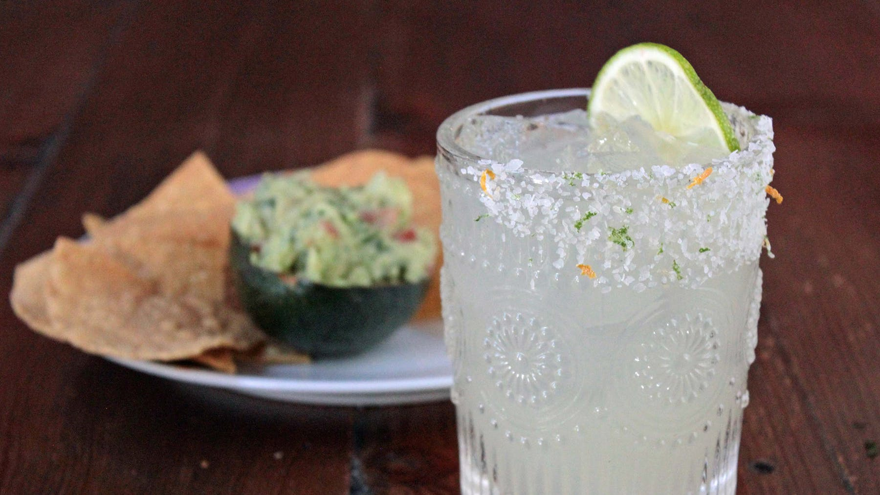 a glass of margarita with lime and guacamole in an avocado with chips on a plate in the back