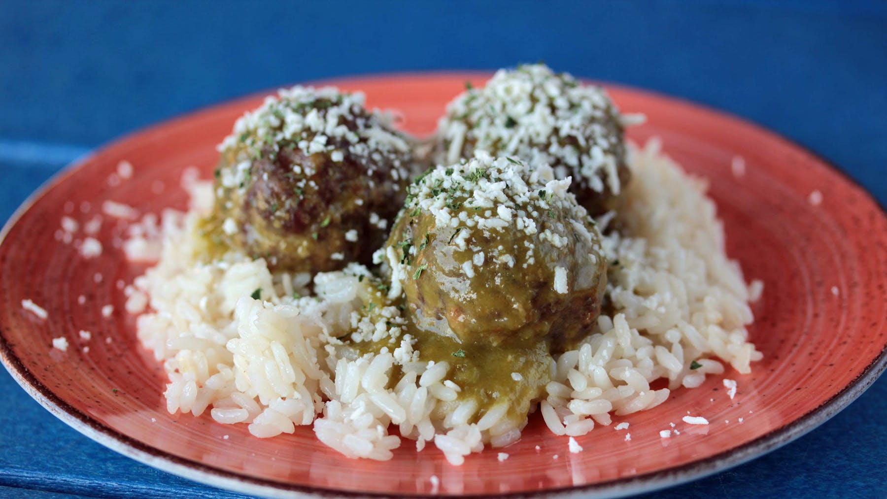 a plate of meatballs on top of rice