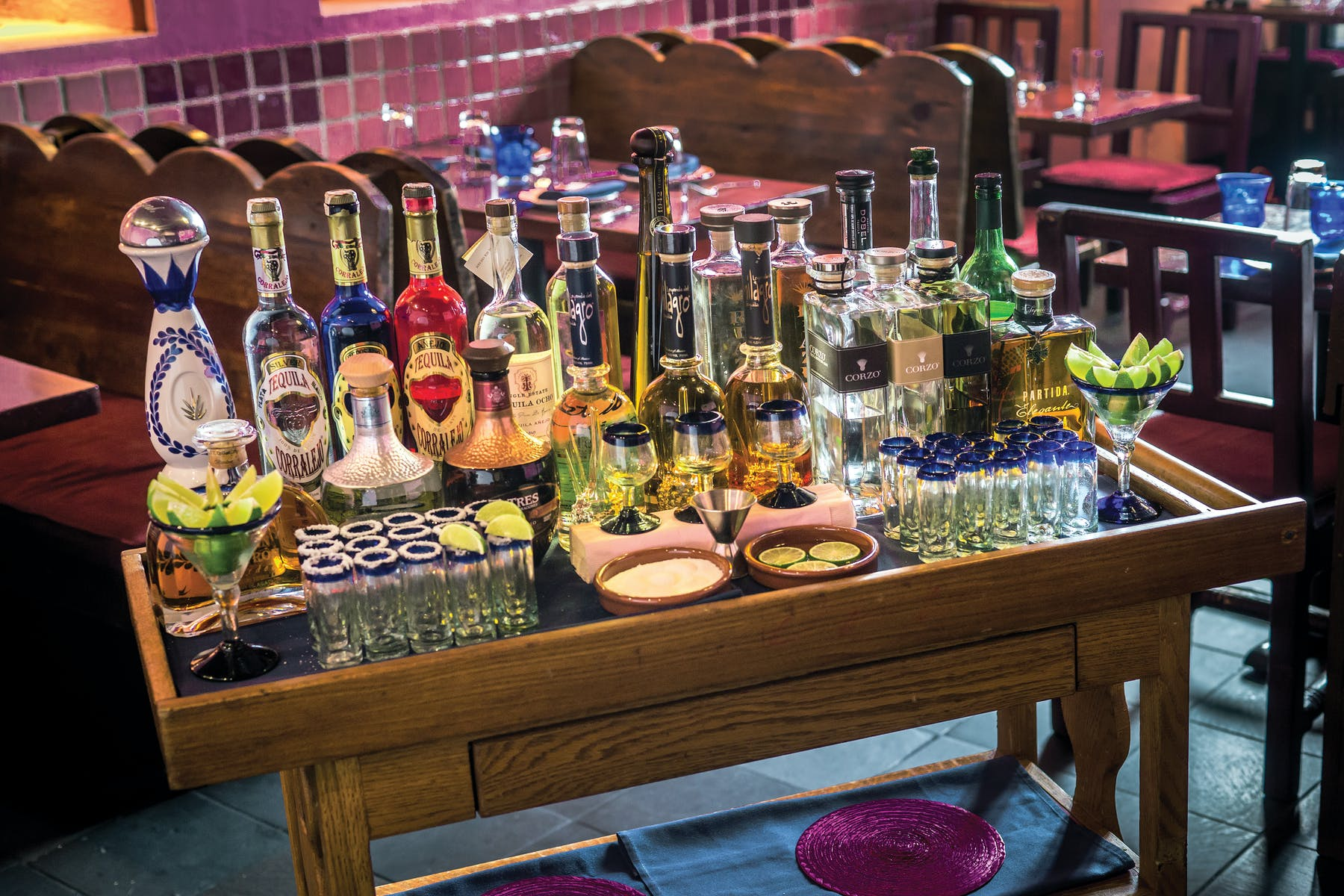 bar table with lots of tequila bottles, tequilla shots and lemons
