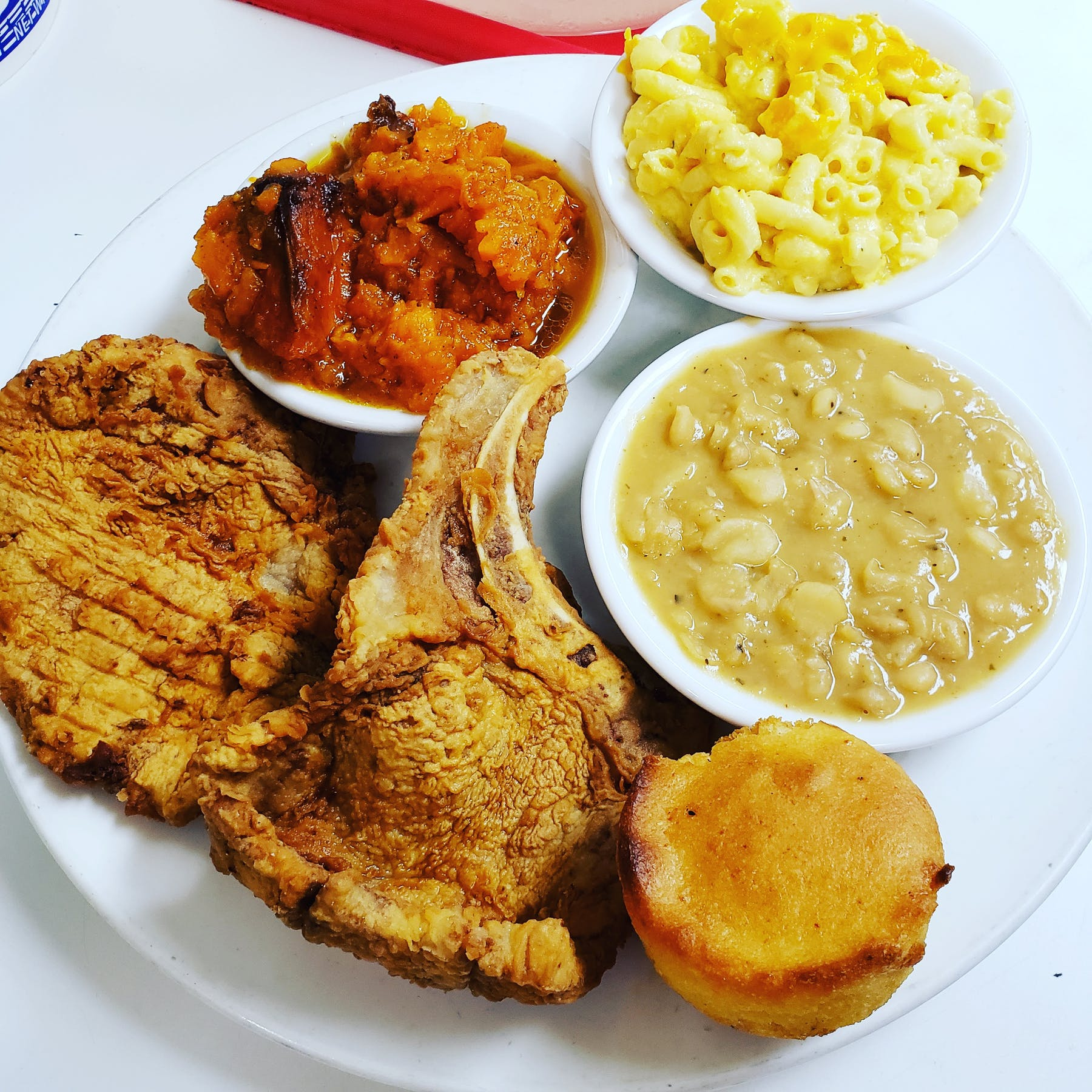 a white plate topped with fried chicken and bowls filled with food