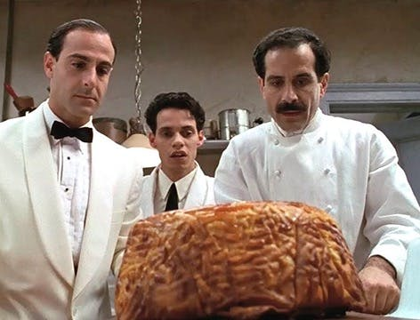 Marc Anthony, Tony Shalhoub standing in front of a large sandwich