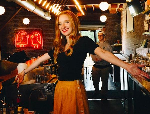woman smiling behind bar