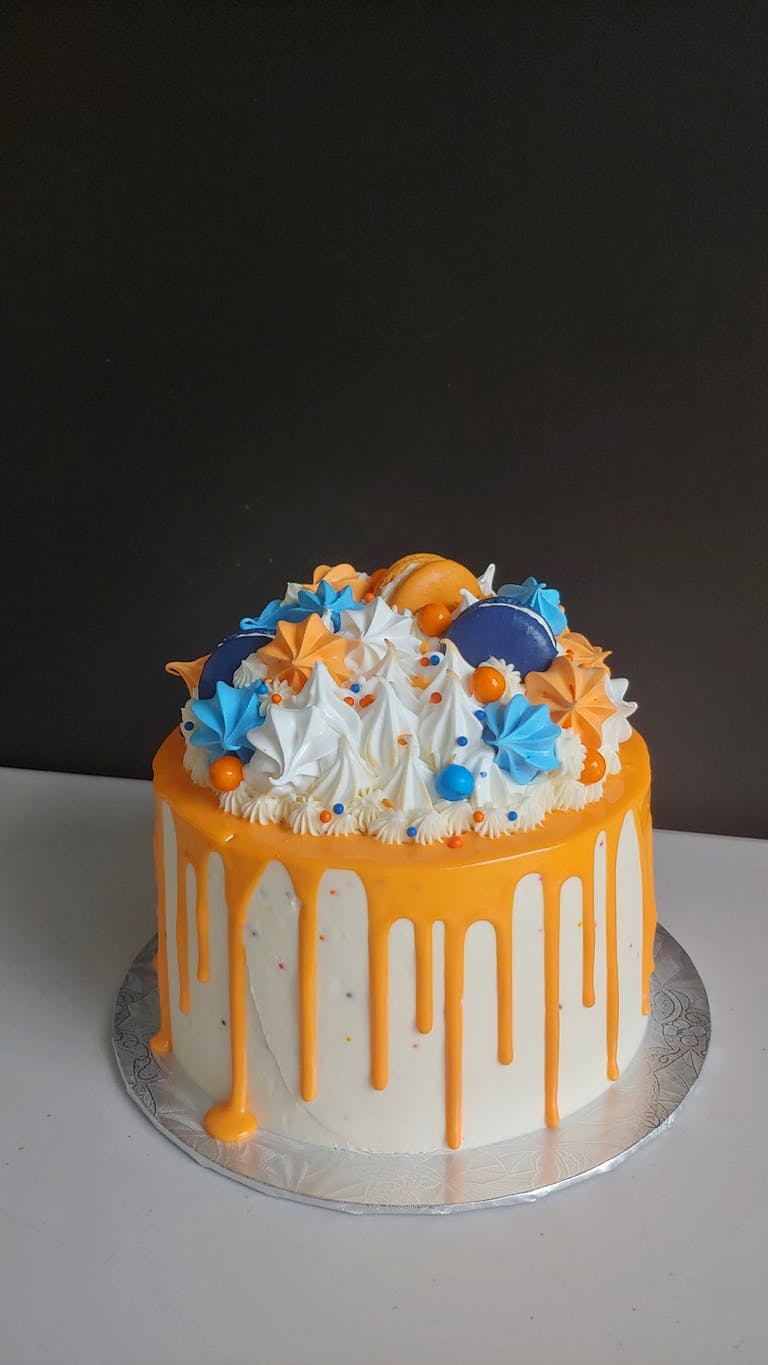 a cake in Oilers colours with orange and blue meringues and macarons
