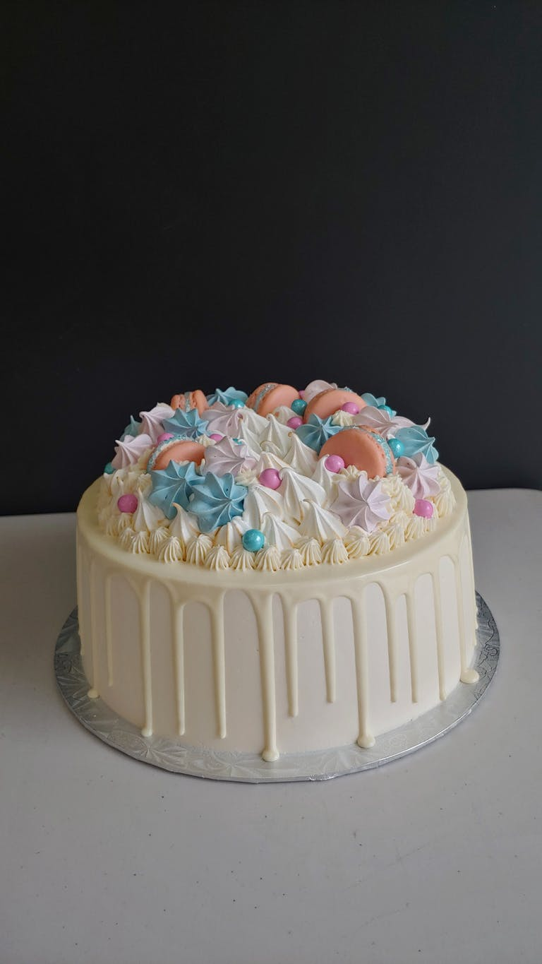 an Epic cake with white chocolate drip and pink macarons and blue and white meringues