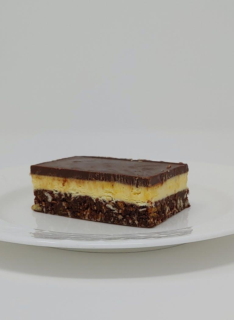 a solitary nanaimo bar on a white plate