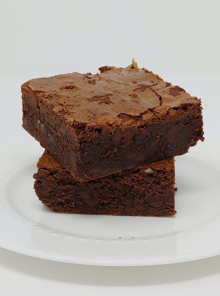 two brownies stacked on a white plate