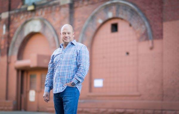Ieuan Evans standing in front of a brick building