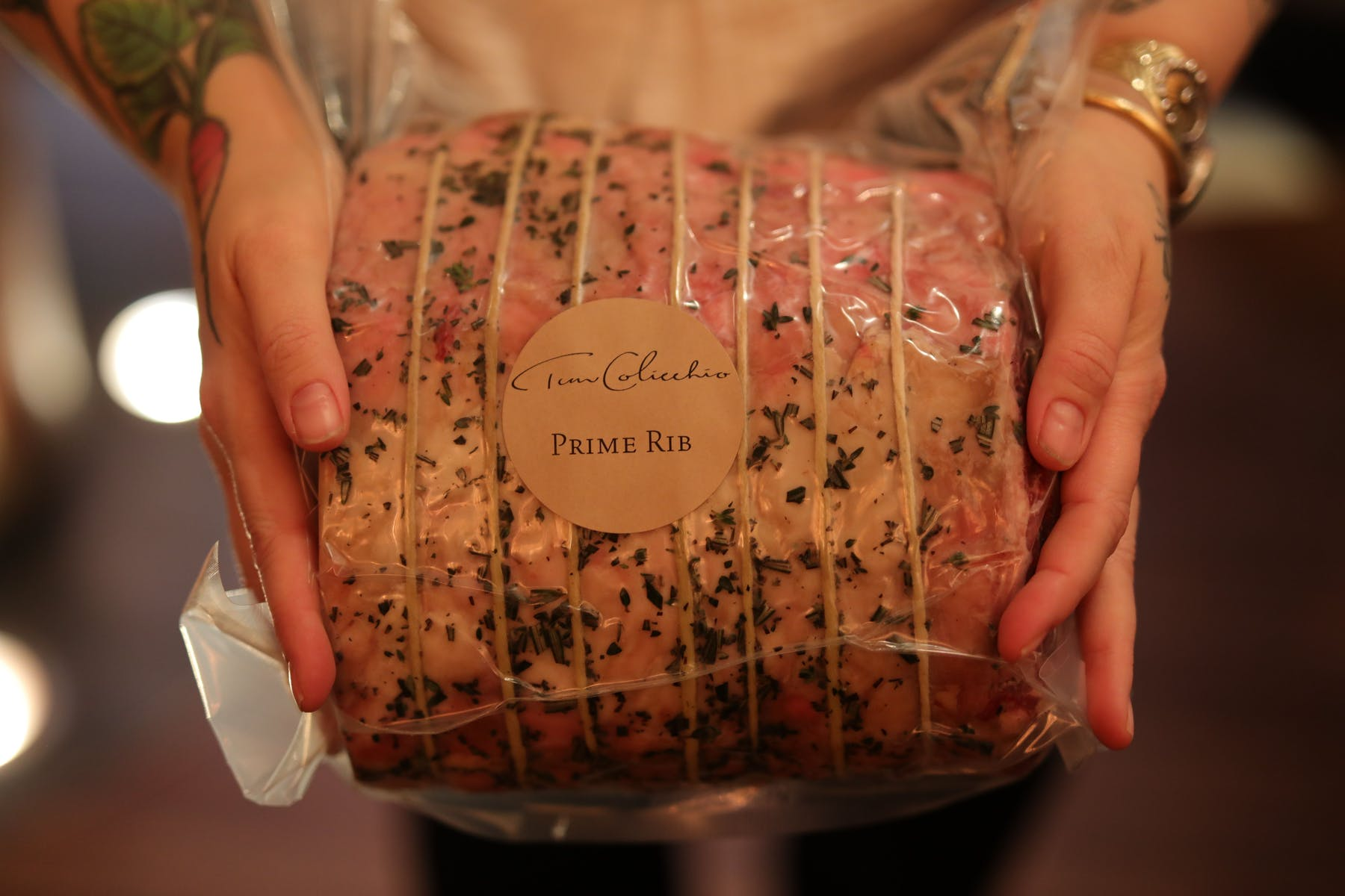 a hand holding a tied and packaged prime rib