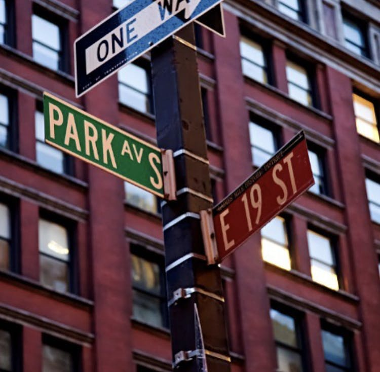 a close up of a street sign in front of a tall building