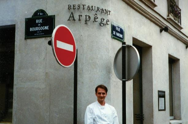 a man standing in front of a sign on the side of a building