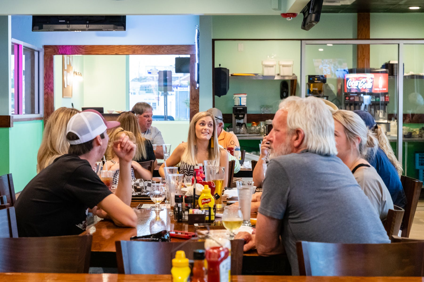 a group of people sitting on a large table at the restaurant