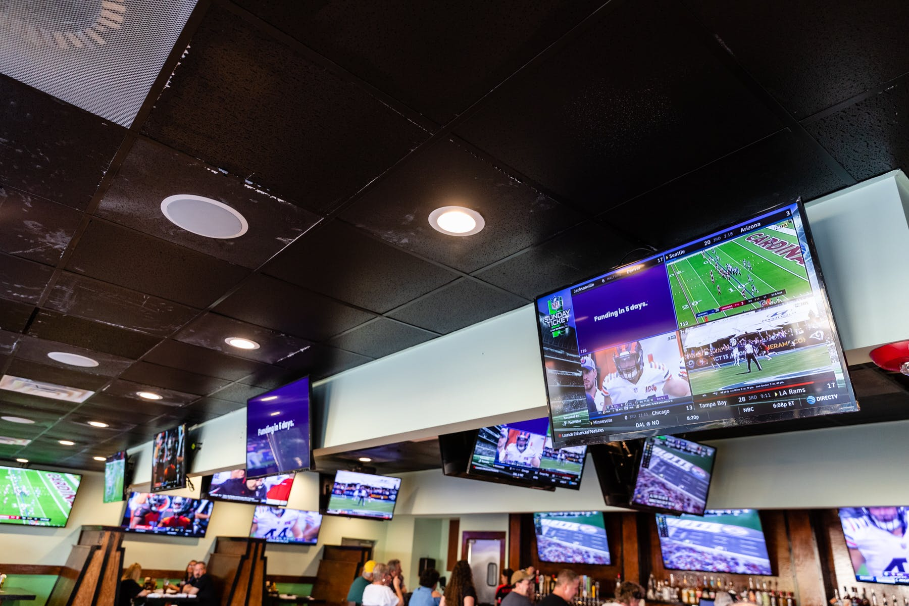 tv screens with football games placed on a wall