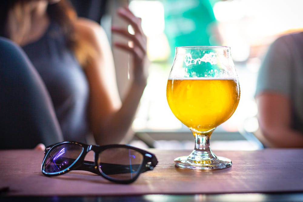 a person sitting at a table with a glass of beer sided with a pair of sunglasses