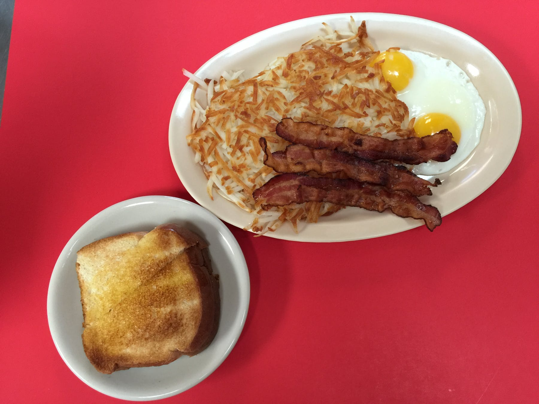 toast, hash brown, bacon and eggs