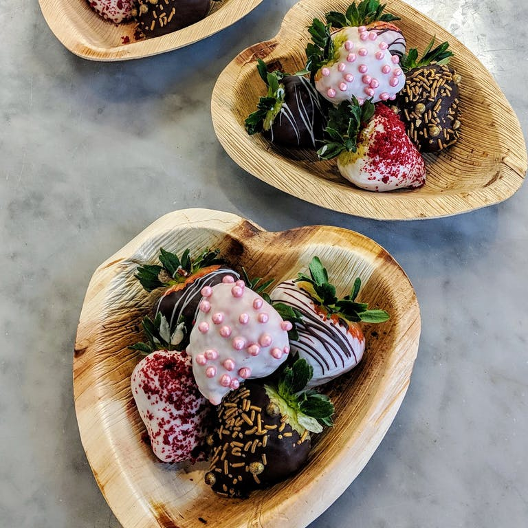 a plate of chocolate dipped strawberries arranged on a table