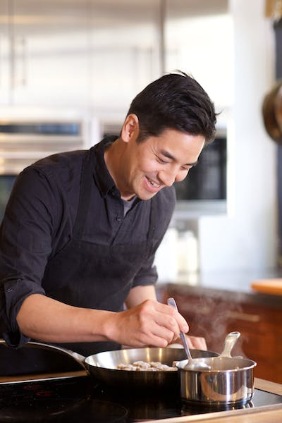 a man cooking in a kitchen preparing food
