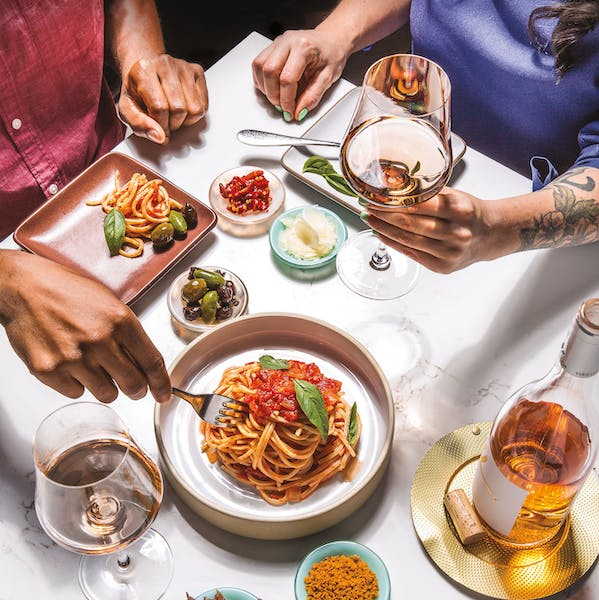 people having lunch with spaghetti and wine