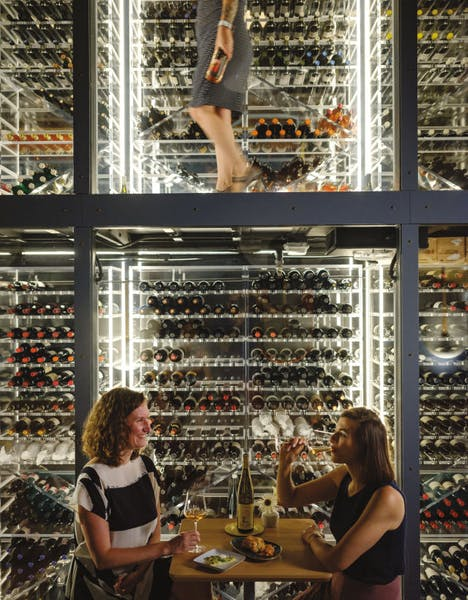 two women having a glass of wine in an enoteca