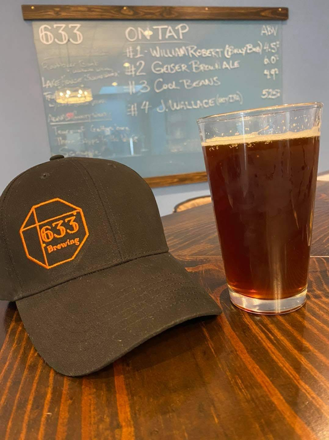 a glass of beer and a hat on a table