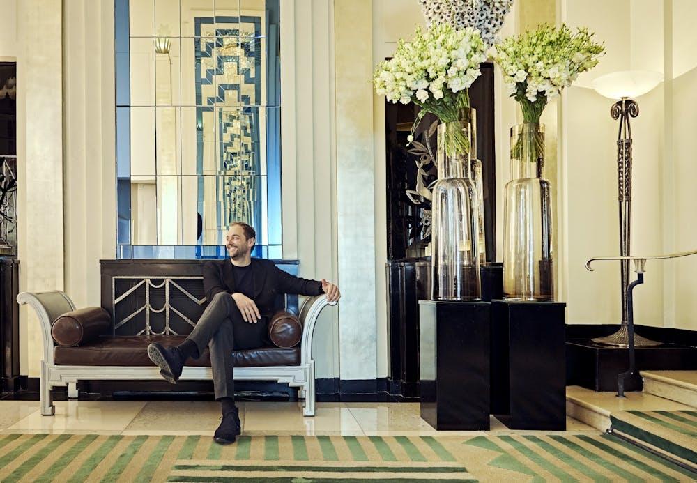 Chef Daniel Humm sitting on a chair in a lobby