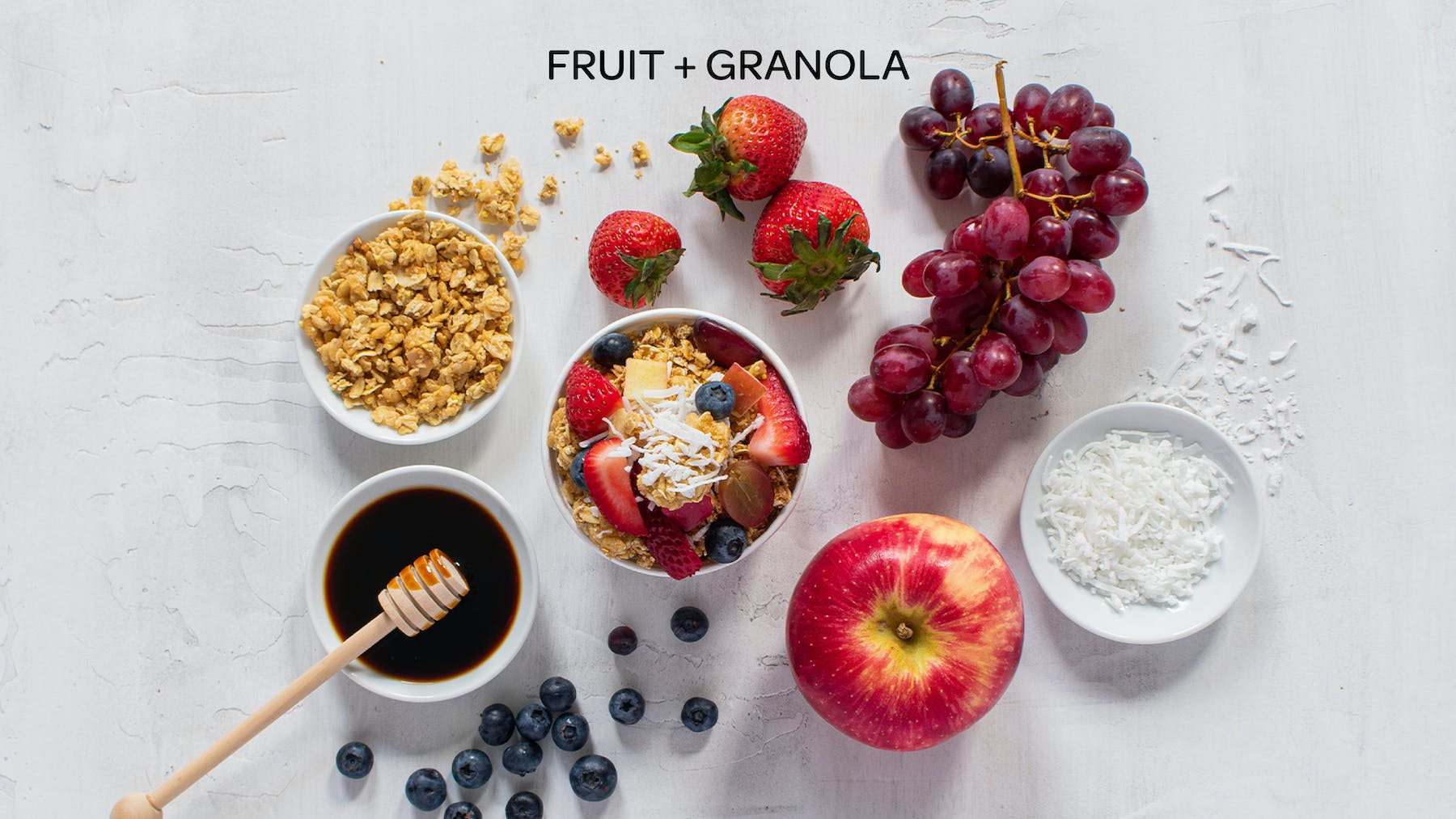 the ingredients of a fruit and granola honeybar laid out on a table