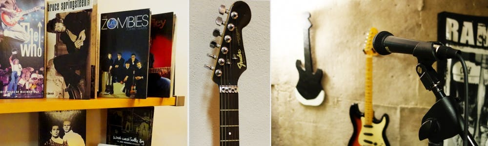 a guitar hanging on a wall, several records on a shelf and a close up of a guitar