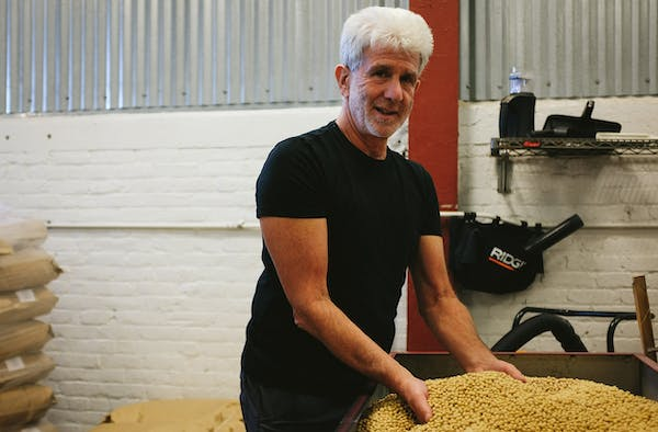 a man holding a pile of grains