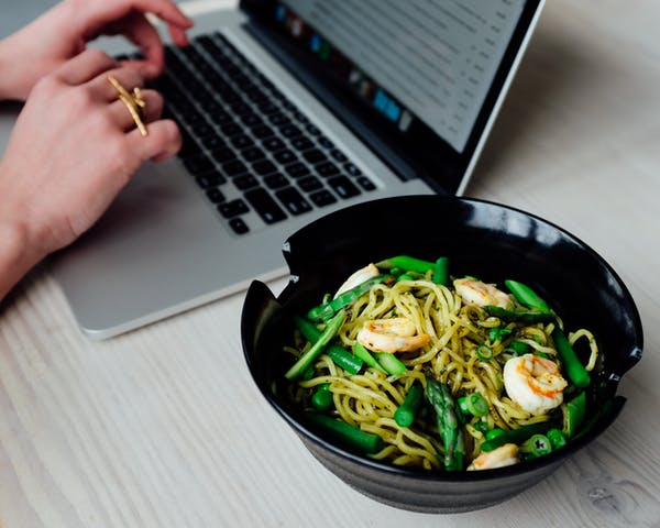 a person working on a mac next to salad
