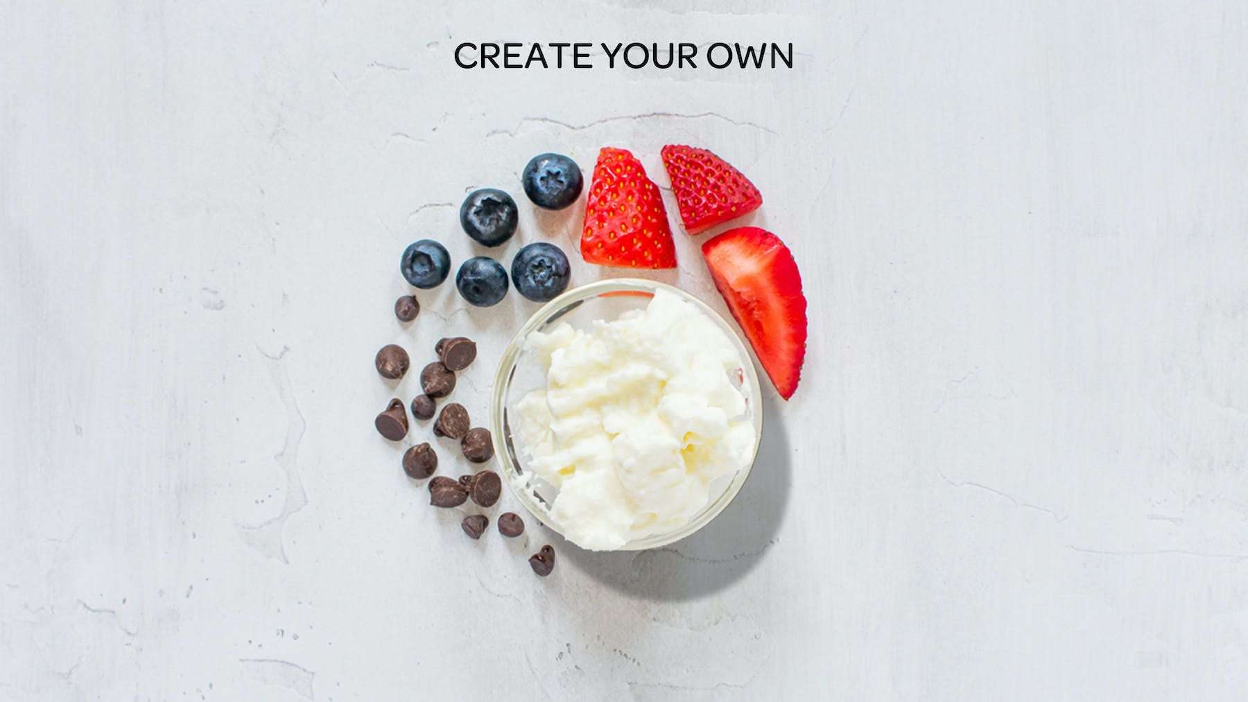 whipped cream, fruit and chocolate chips spread out on a table to represent a create your own honeybar
