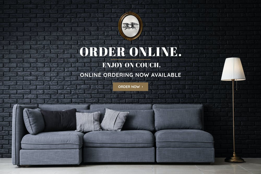 a sofa in front of a brick wall