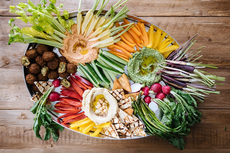 a wooden table topped with lots of fresh fruits and vegetables