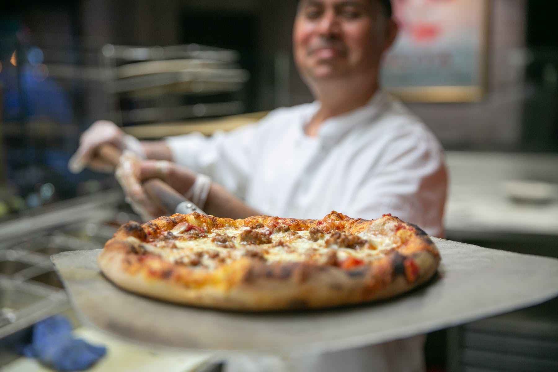 a chef showing a pizza