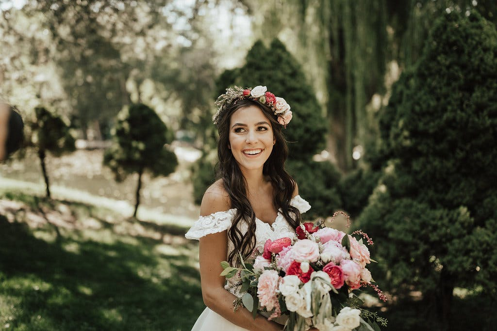a bride with a bouquet of flowers smiling at the camera