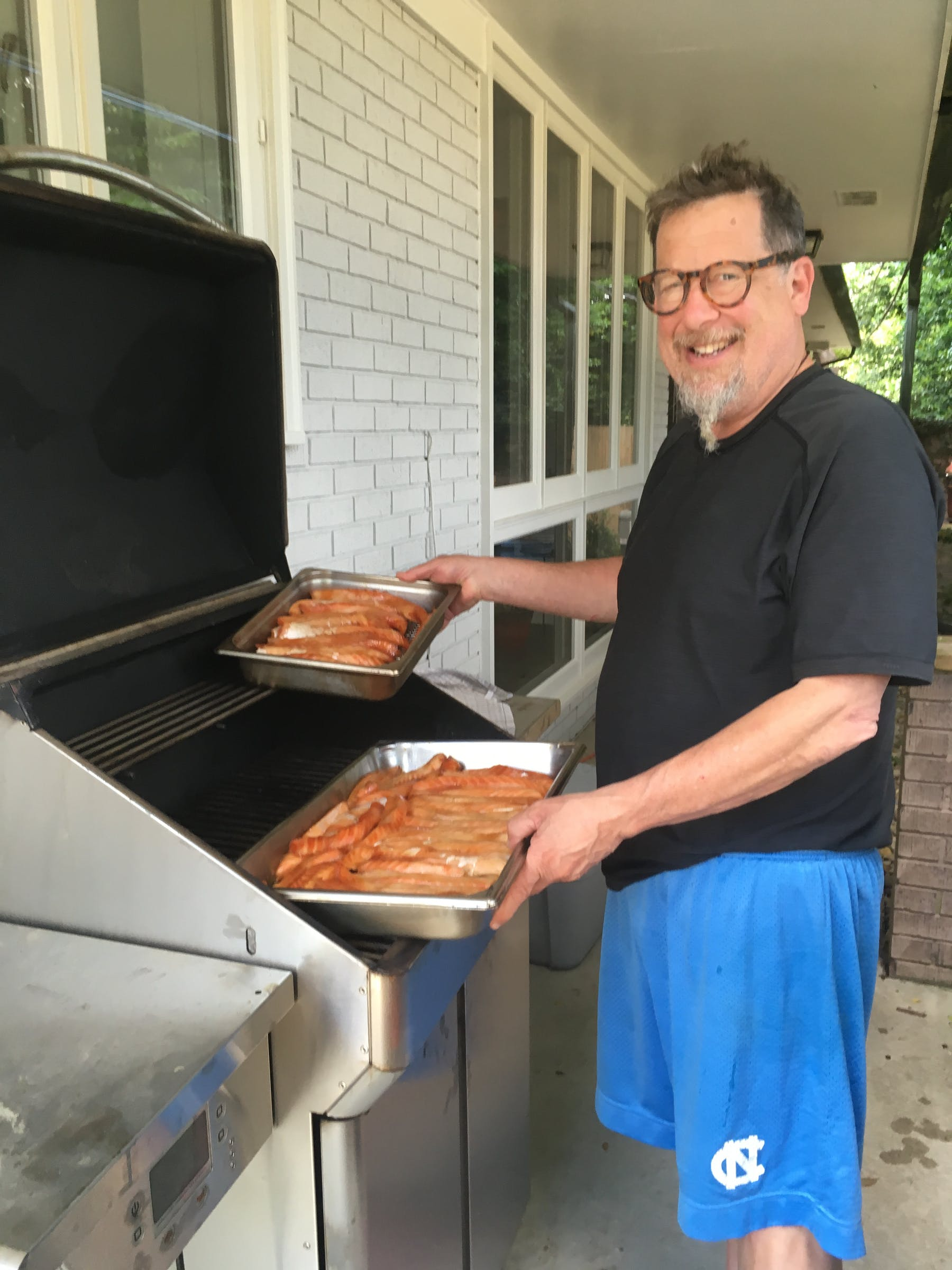 a man holding a pizza on a grill