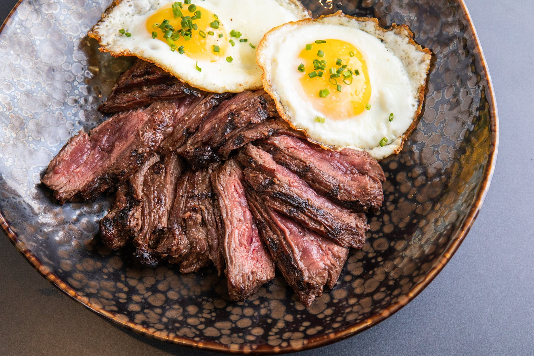 a plate with grillled meat and eggs