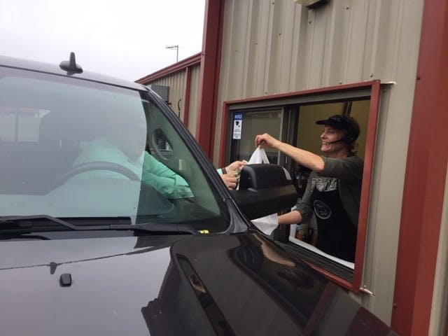Food being passed out through a drive through window at Van's Pig Stands in Purcell Oklahoma