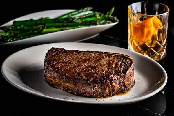 a piece of steak on a plate sided with a drink
