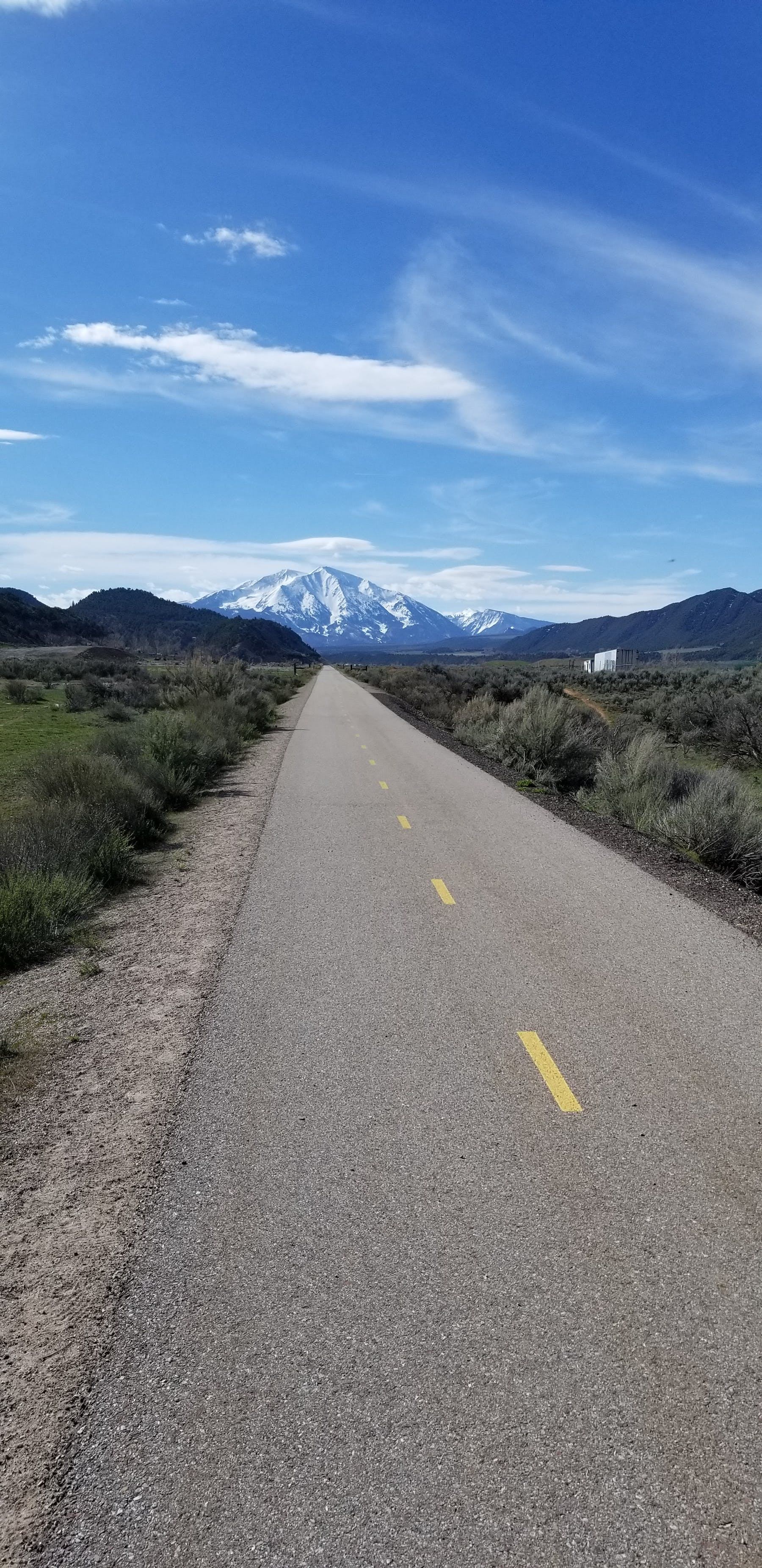 an empty road with a mountain in the background