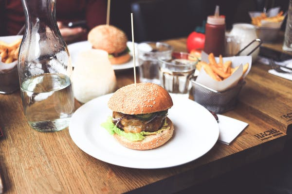 a table topped with  burgers