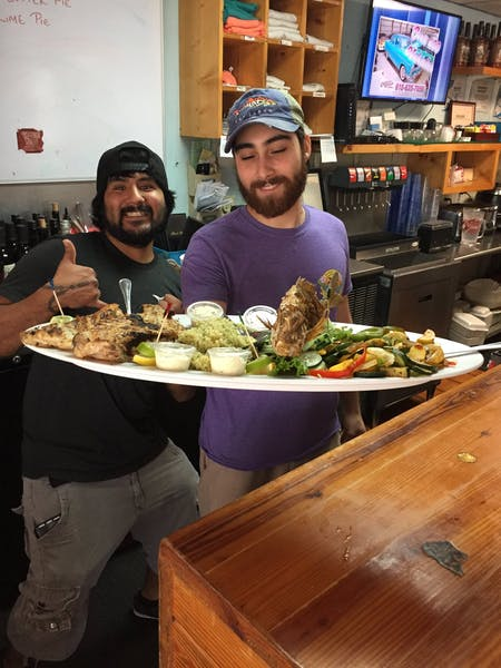 two men holding a large plate with fish, rice, lettuce and sauces