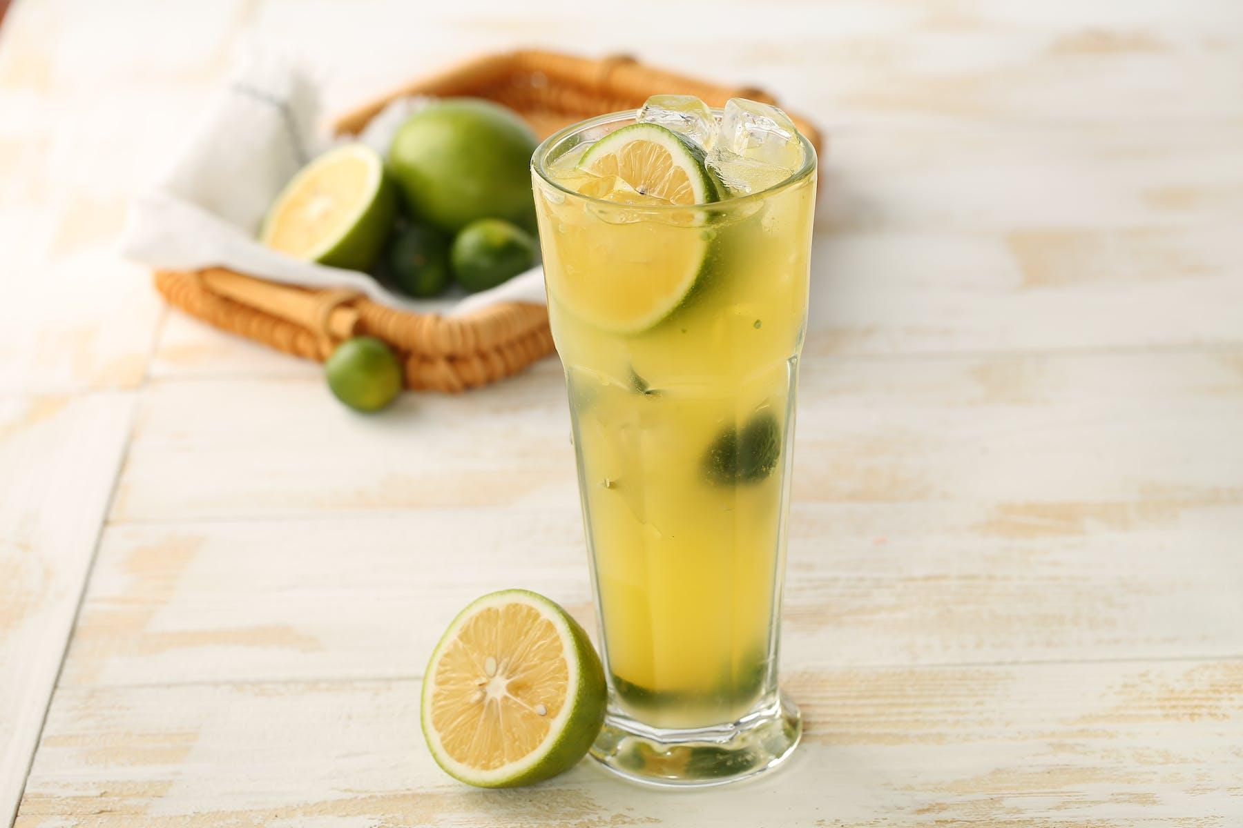 a glass of lemonade sitting next to a sliced lemonade