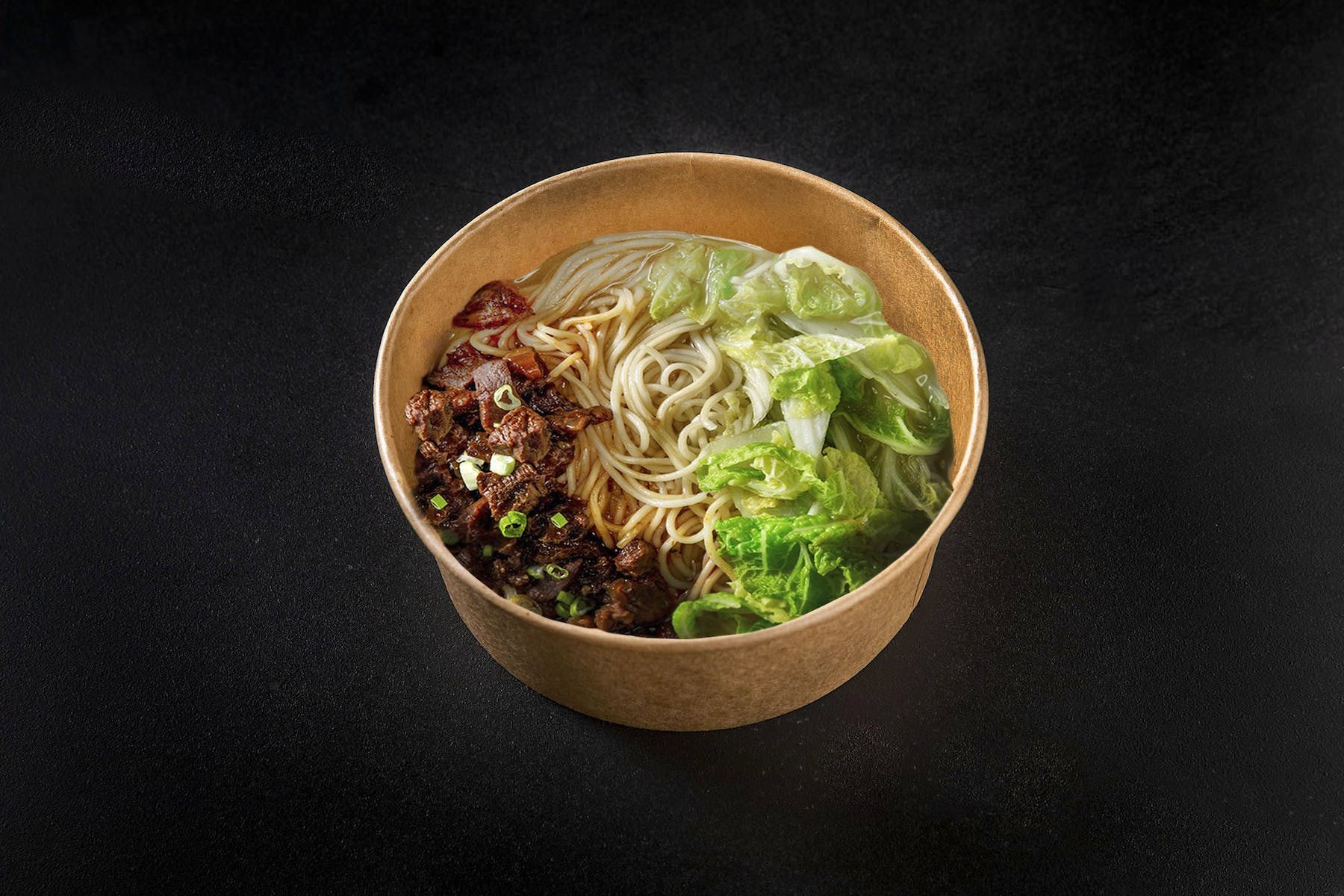 a bowl of noodles, meat, and veggies